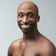 A headshot of a bald black man, smiling