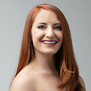 A heashot of a white woman with long, red hair smiling