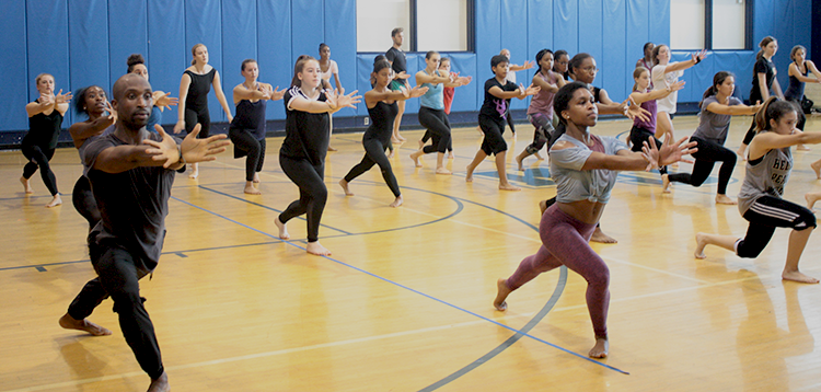 Large group of dancers lunge and reach to the front with both arms