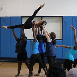Student dancers in a gym performing a lift